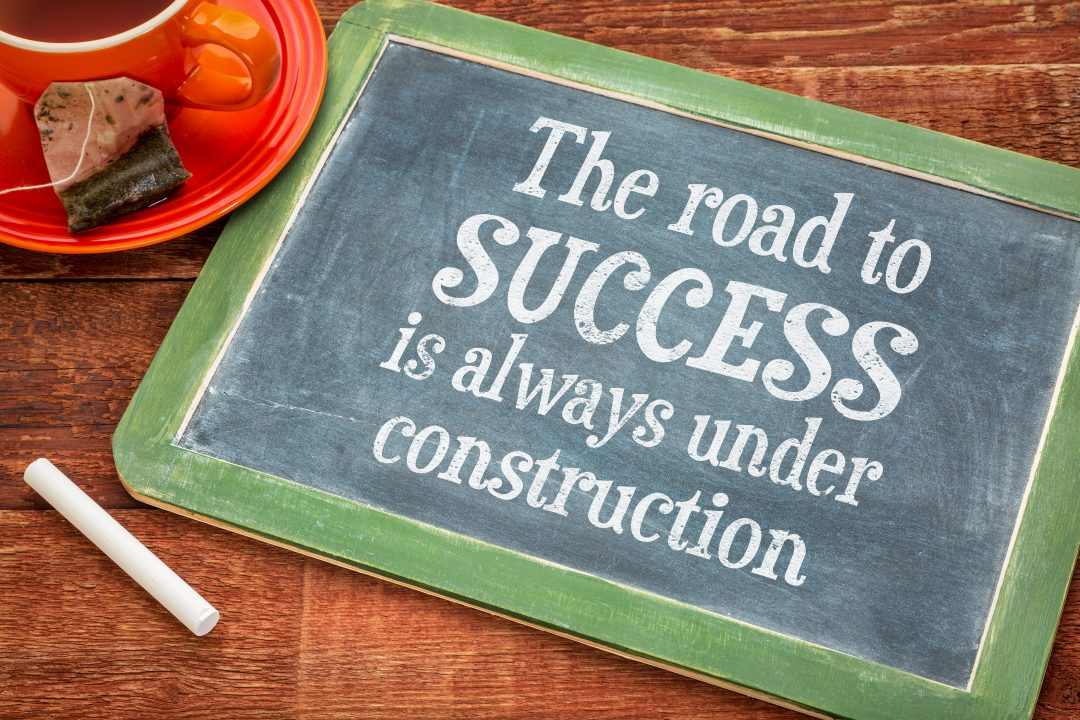 The road to success is always under construction - motivational text on a slate blackboard with chalk and cup of tea